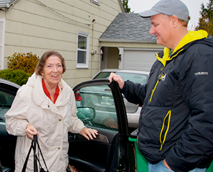 a man holding a car door open for an older woman