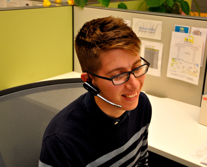 smiling person speaking on a telephone headset
